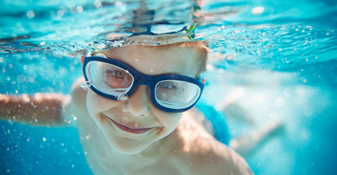 child with goggles in under water