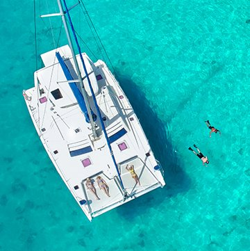 Aerial view of catamaran with people snorkeling