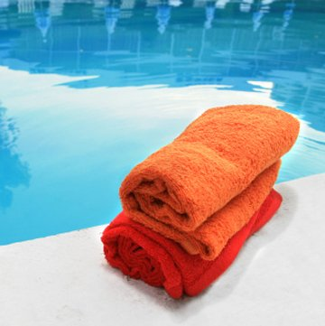 folded orange towels poolside