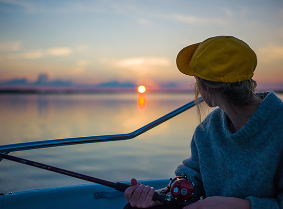 Woman holding fishing pole on boat with sun setting in the back