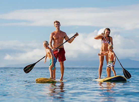 Couple paddle-boarding on two boards with children