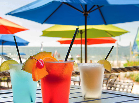 multicolored tropical drinks sitting on a table under umbrella