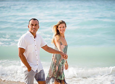 Couple holding hands as they walk by the ocean shore