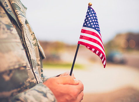 Man holding an american flag with a uniform