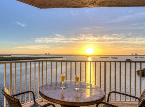 lovers key resort balcony with table, two chairs and two glasses of champagne overlooking the bay