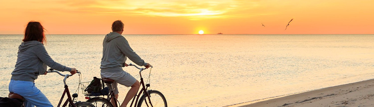 man riding a bicycle at a beach during sunset