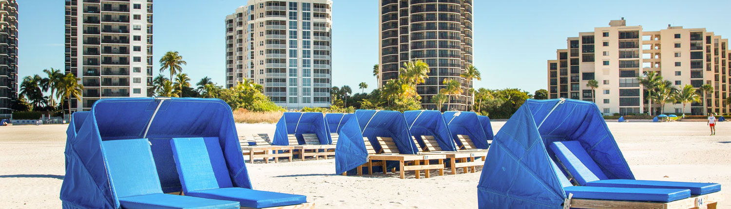 blue chair cabanas on a white sand beach with a skyline of buildings