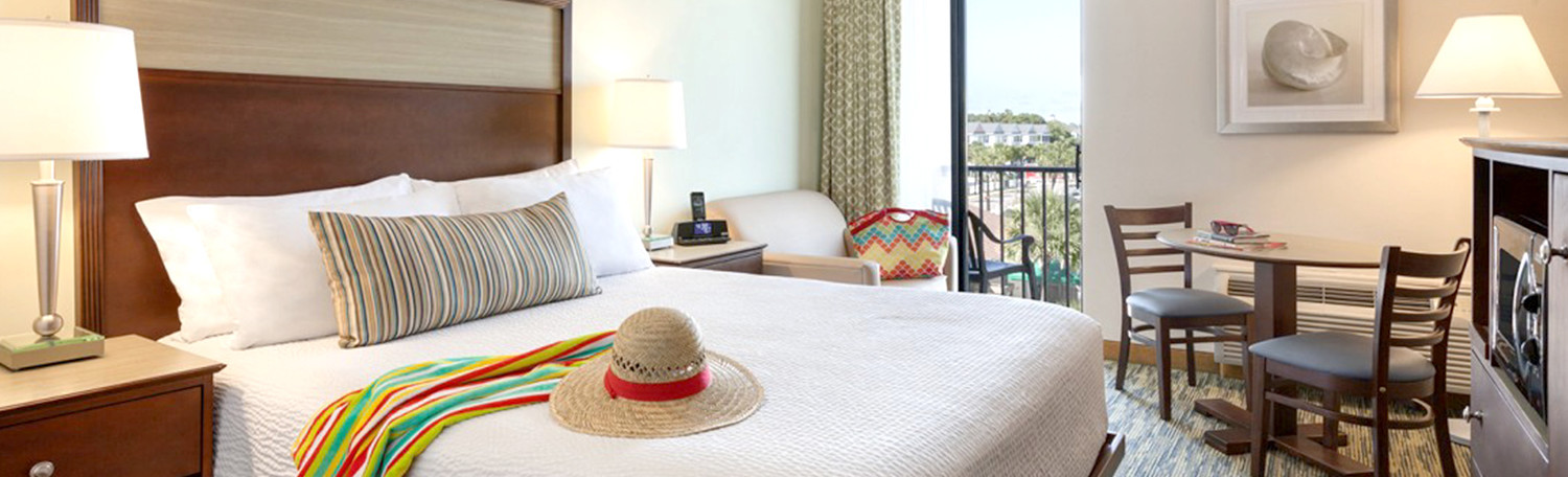 Bed with two nightstands and lamps, hat on bed with sarong