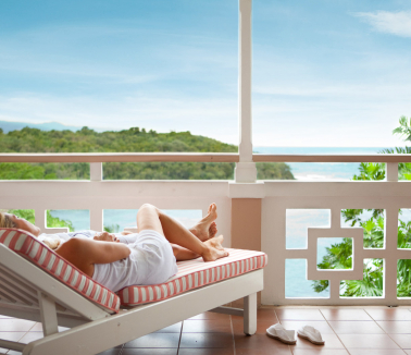Couples Sans Souci couple lounging on balcony overlooking the beach