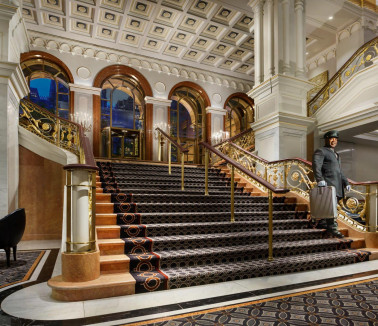 Lotte New York Palace staircase with bellman