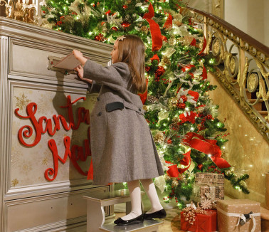Little girl adding letter to santa in mailbox