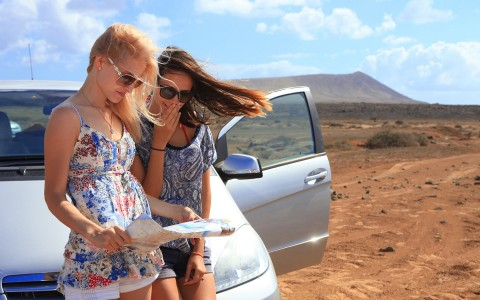 two girls leaning on car reading a map