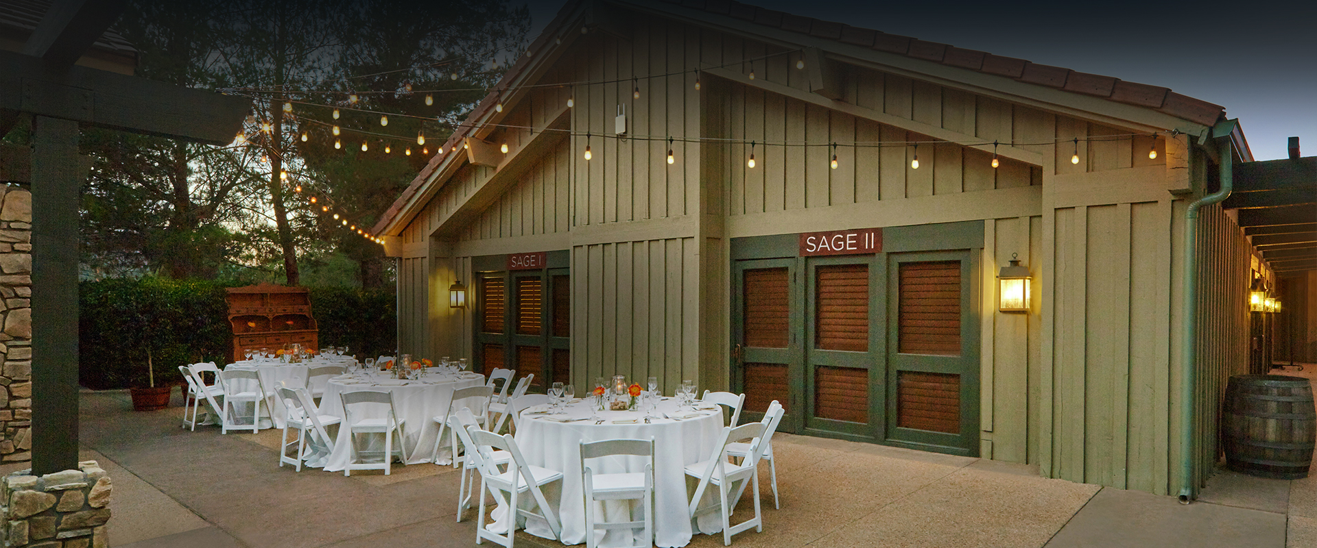 white tables and chairs set up outside a barn with lights hanging down
