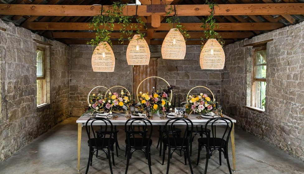 decorative light pendants overtop a table decorated with florals