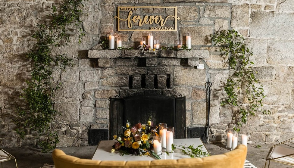 stone fireplace decorated with greenery, candles, and a sign