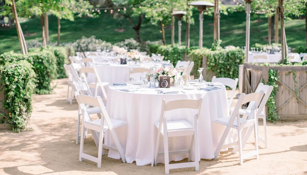 white tables and chairs set up outside for an outdoor wedding reception