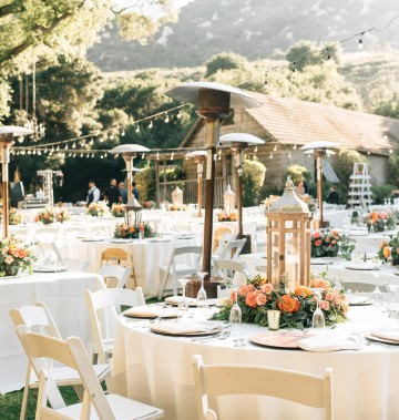 outdoor wedding tables with white tablecloths, string lights, and heaters