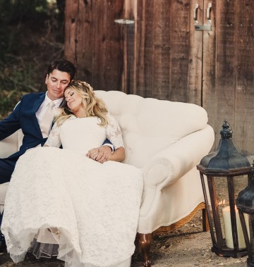 bride and groom sitting on a white couch outside a barn