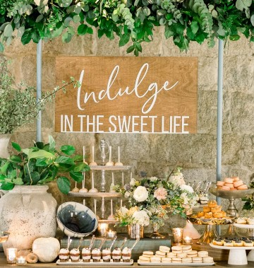wooden sign above a dessert table at a wedding