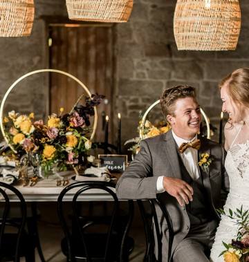 bride and groom sitting at a wedding reception table with colorful floral arrangements
