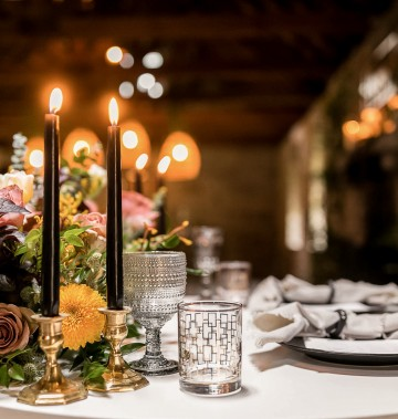 close up of flowers and candles on a wedding reception table indoors