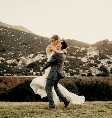 groom picks up his bride and kisses her in a field