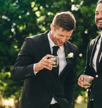 two men in suits holding drinks and laughing