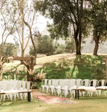 outdoor wedding set up with white chairs and wooden accents