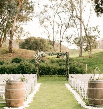 outdoor wedding ceremony with a wooden centerpiece, wooden barrels, and white chairs
