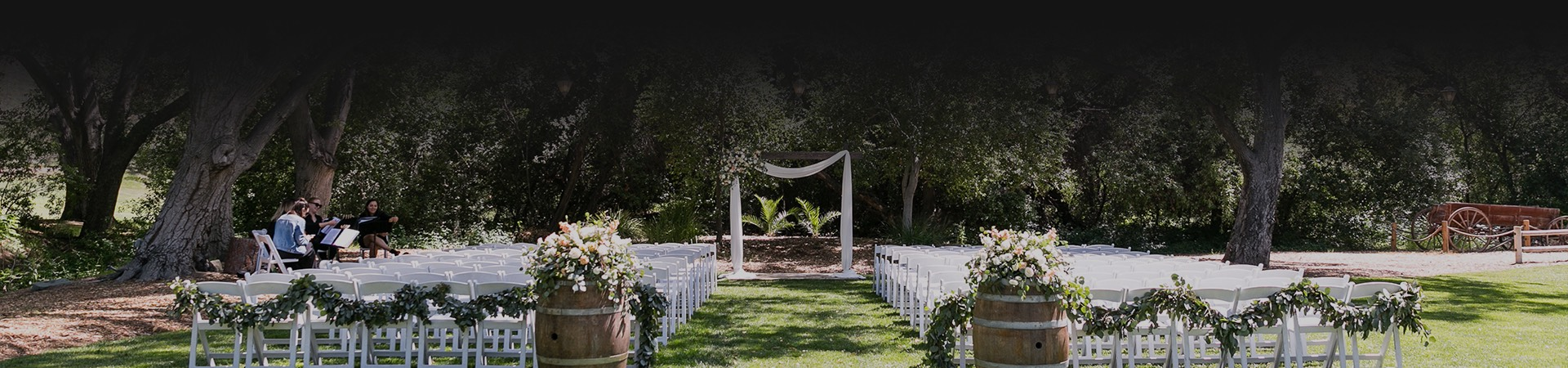 wedding ceremony with white chairs set up outside