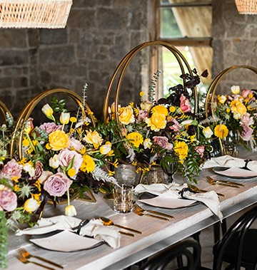 wedding table decorated with utensils, plates, and colorful floral arrangements