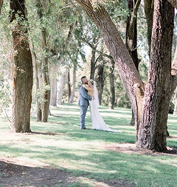 bride and groom holding each other surrounded by tall trees