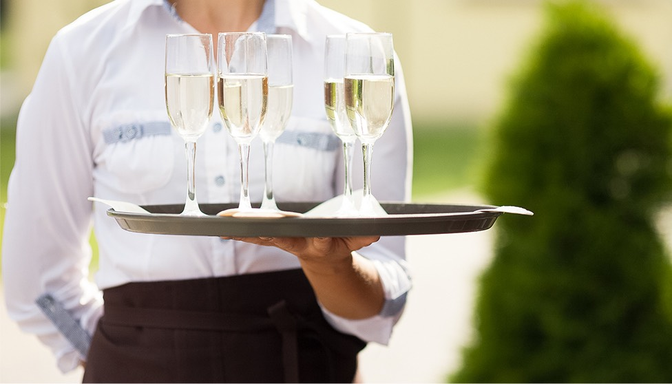 waitress holding a tray of champagne glasses