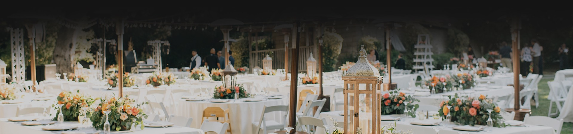 wedding reception tables set up outside with white tablecloths