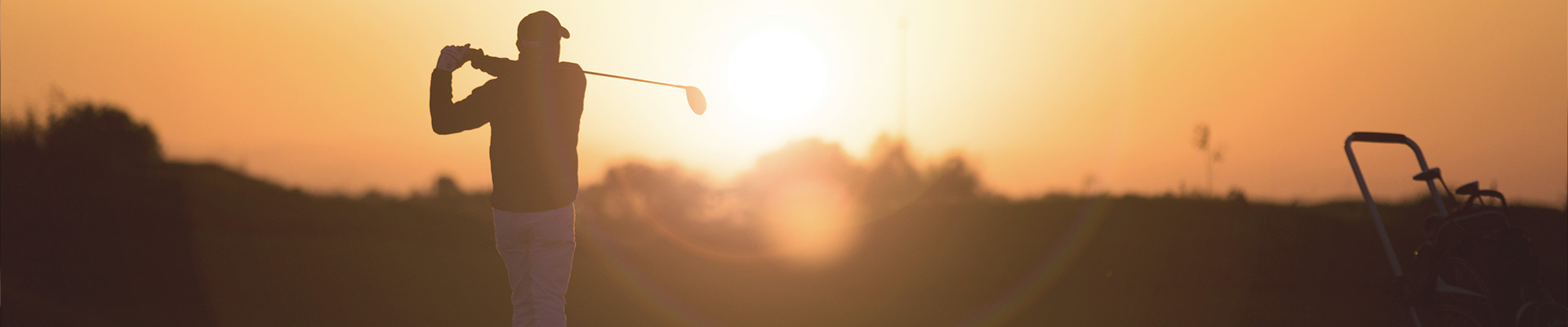 man playing golf in a sunset