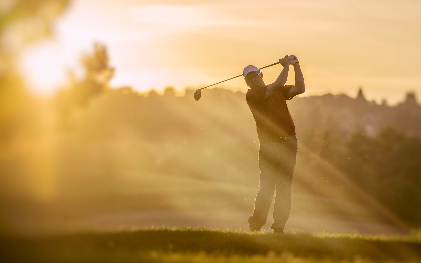 man teeing off in the sunset