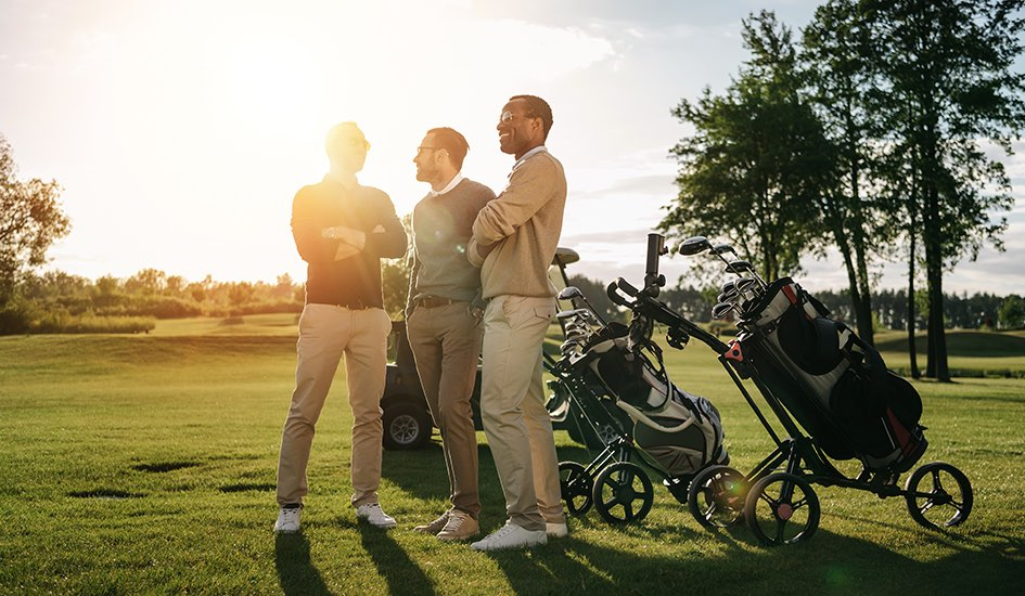 three golfers standing next to their bags talking on the course