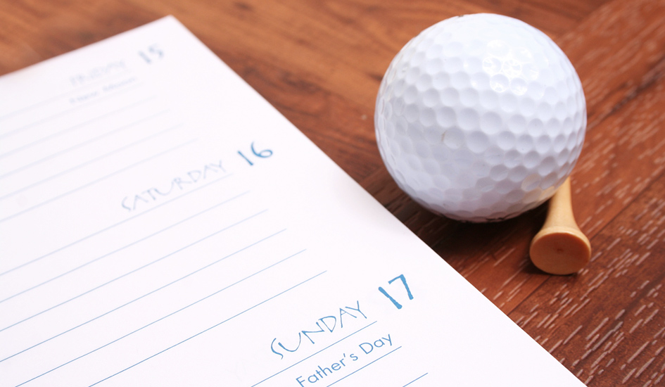 a calendar with a golf ball and tee next to it