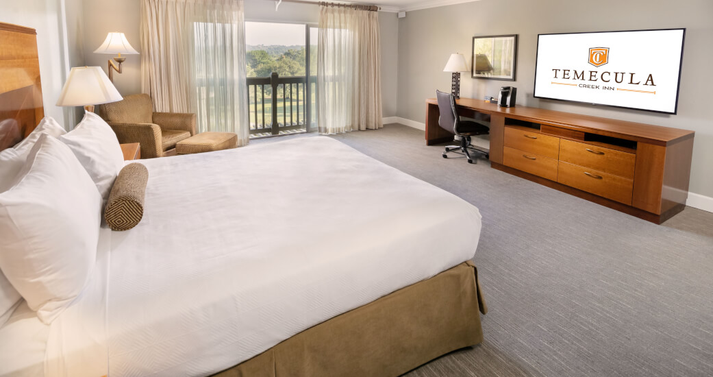 room with king bed and golf course view