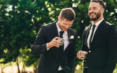two men in tuxedos laughing over a drink
