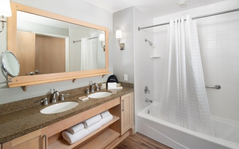 large bathroom with double sinks and shower/tub combo