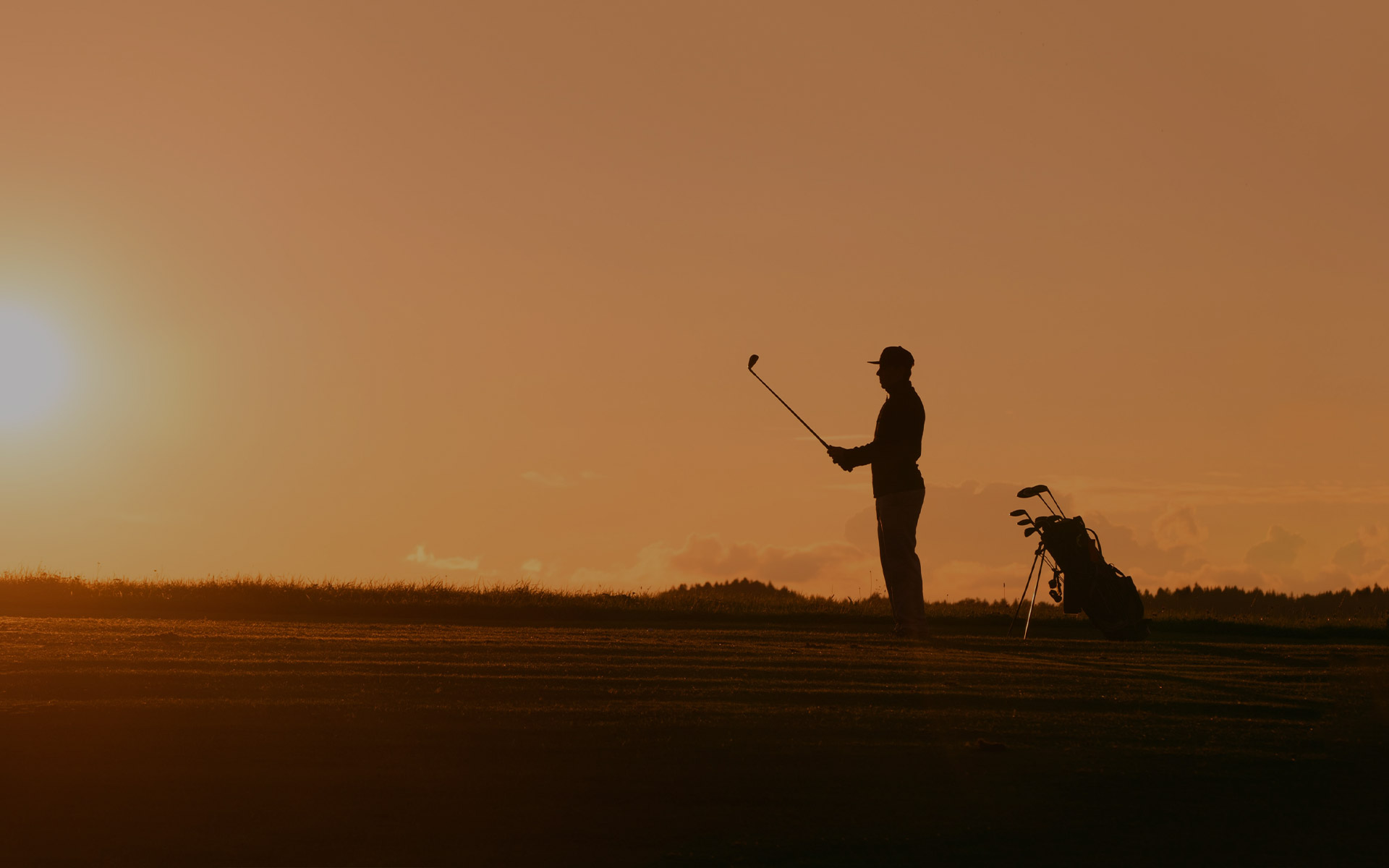 silhouette of a person playing golf