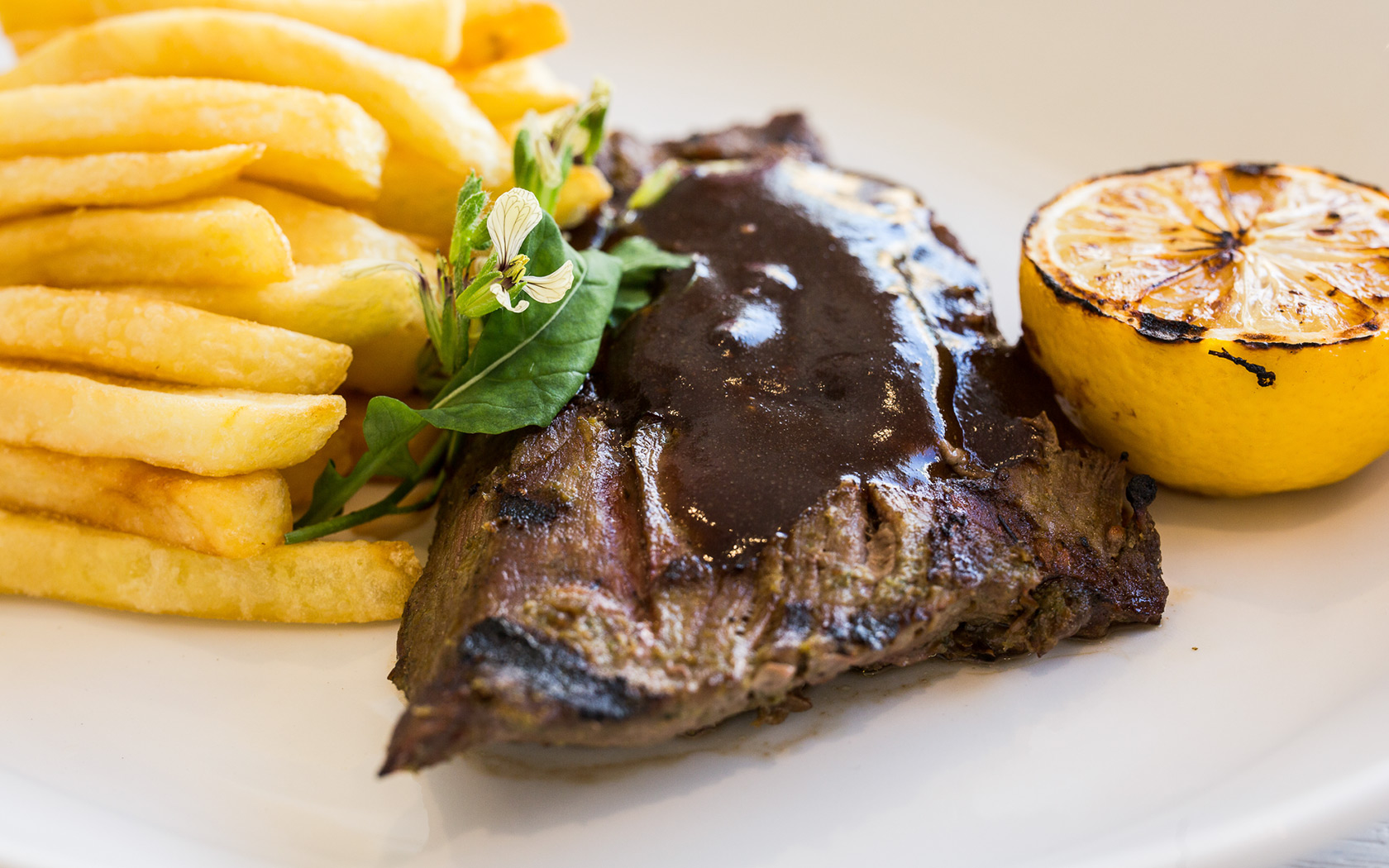 a steak with brown sauce next to a sliced charred lemon and french fries