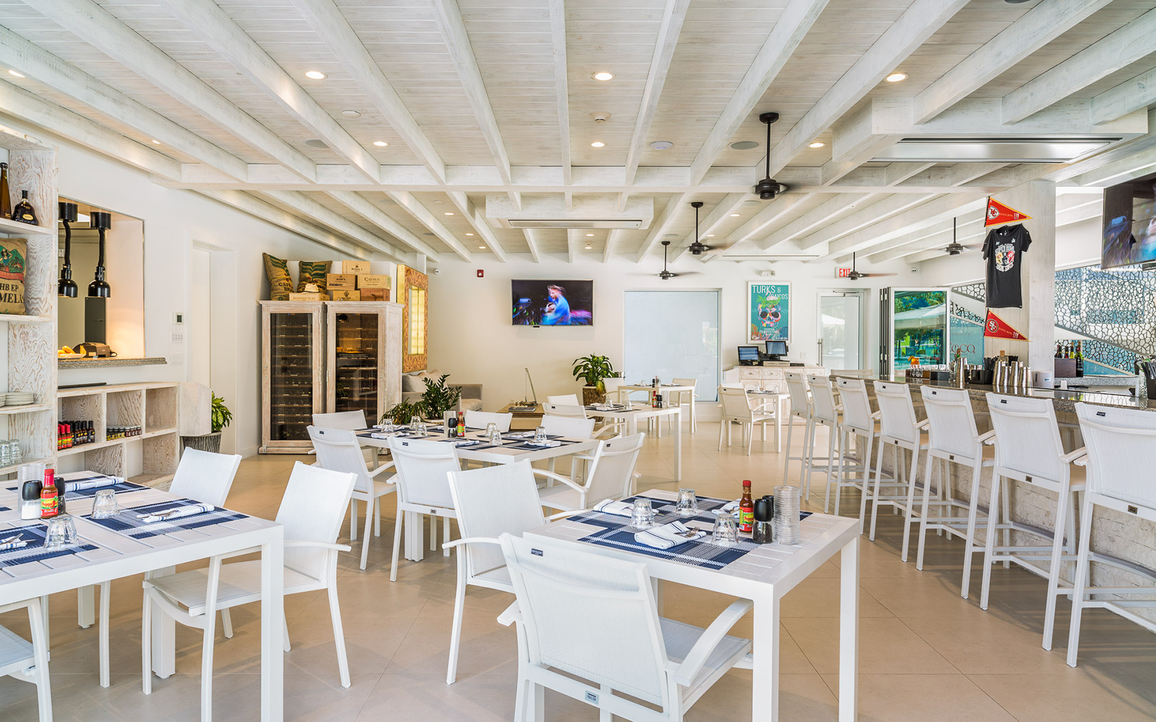 indoor dining area with white tables and chairs with a bar and various TVs