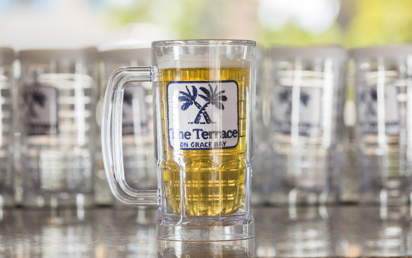 insulated tumbler filled with beer with the terrace on grace bay logo