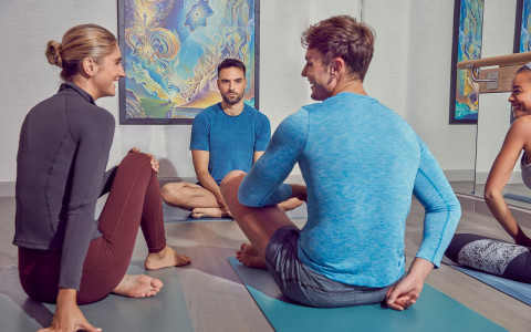 four people inside of yoga studio siting on their matts