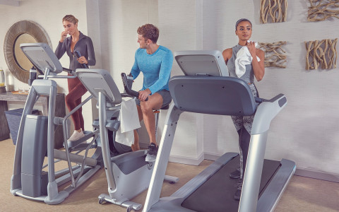 three people doing cardio at the hotel gym