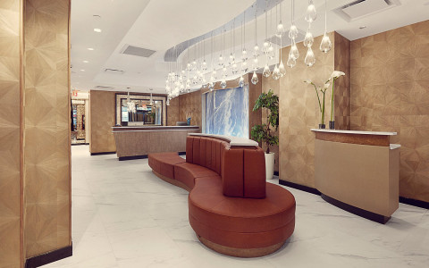 hotel lobby with a seating area and a large lighting fixture hanging from the ceiling