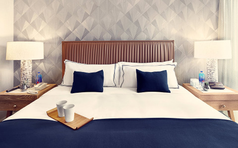 A king bed with white and blue pillows with a nightstand on each side.