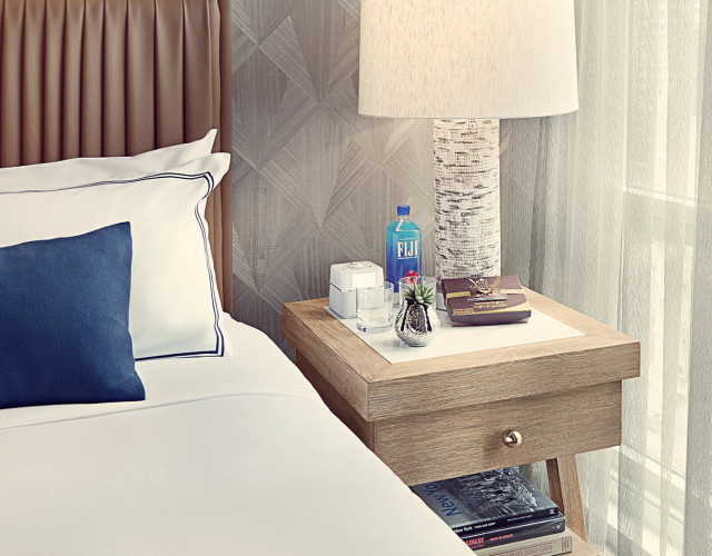 close up of a hotel bed and nightstand with water and chocolates